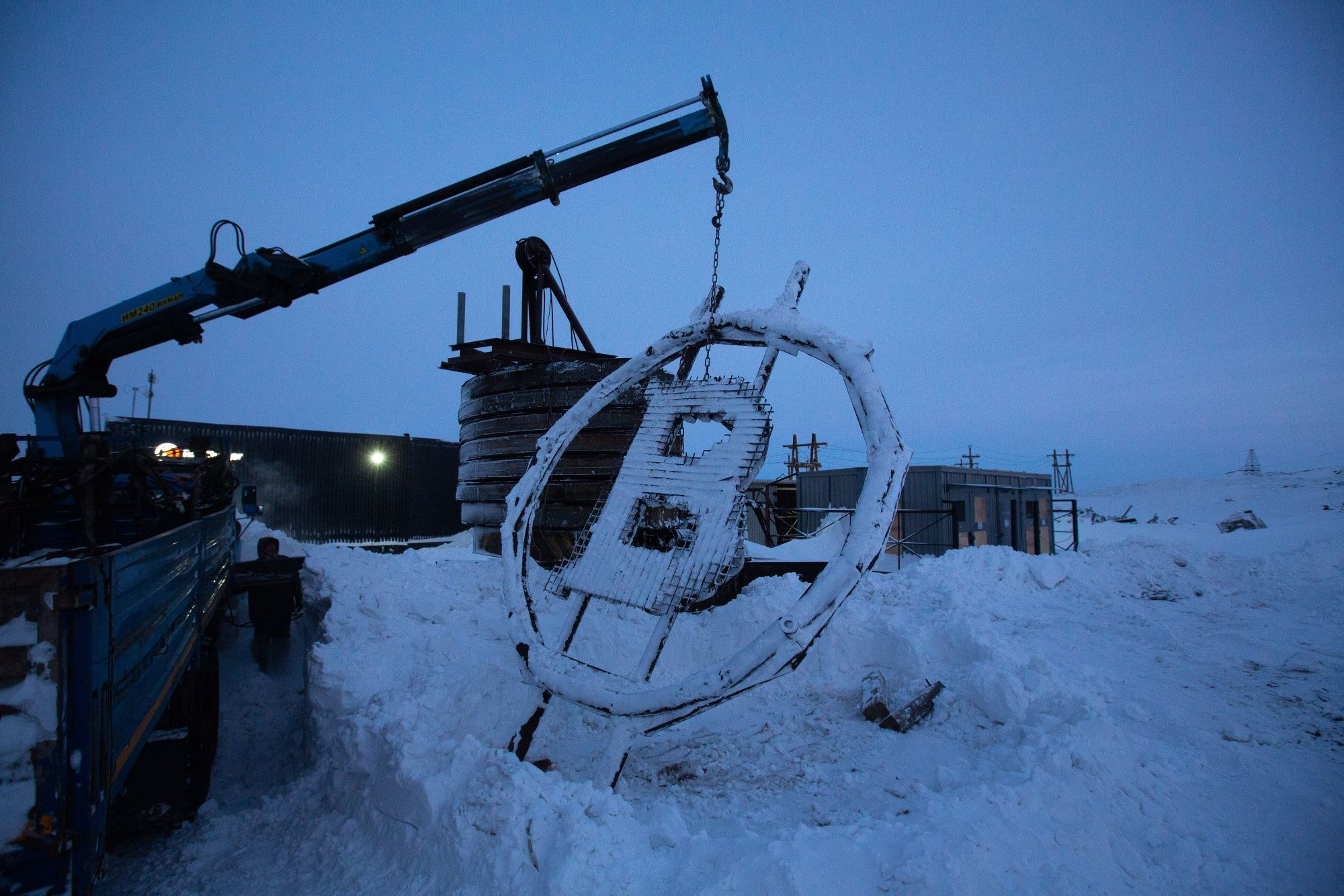 A crane arm lifts a bitcoin sculpture made from scrap metal as it is installed outside the BitCluster cryptocurrency mining farm in Norilsk, Russia, on Sunday, Dec. 20, 2020. Norilsk may soon be famous for a different type of mining — it now hosts the Arctic's first crypto farm for producing new Bitcoins. Photographer: Andrey Rudakov/Bloomberg